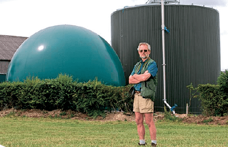 Dr Stephen Temple standing in front of his anaerobic digester